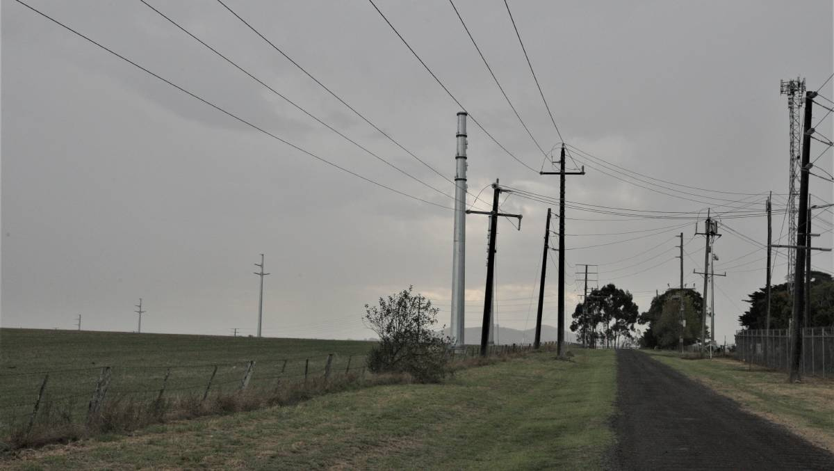 Visual impact: Metal pylons erected to carry transmission lines from the Salt Creek wind farm stand over standard power poles near the Terang terminal station.